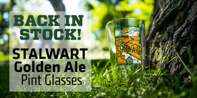 Image of a Stalwart pint glass in the grass with text that reads 'Back in Stock - Stalwart Golden Ale Pint Glasses'